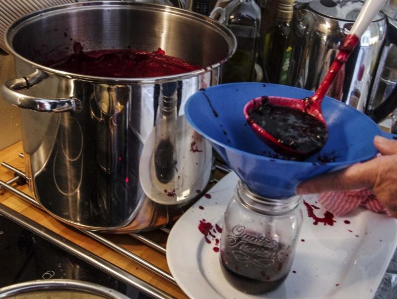 Tøm syltetøyet på de rene glassene som du plukker rett ut av oppvaskmaskinen,. Sørg for at du ikke søler på kanten av glasset ved å bruke en grov trakt. (Her bruker vi en avskåret bensintrakt fra Biltema). Det er viktig at kanten er ren for å unngå luft og bakterier i syltetøyet!