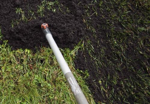 Spre ut toppdress i et ca. 5 mm tykt lag med en jernrive. Der du har 'spiket' rakes det jo litt ned i hullene og bidrar med porøsjord og næring.