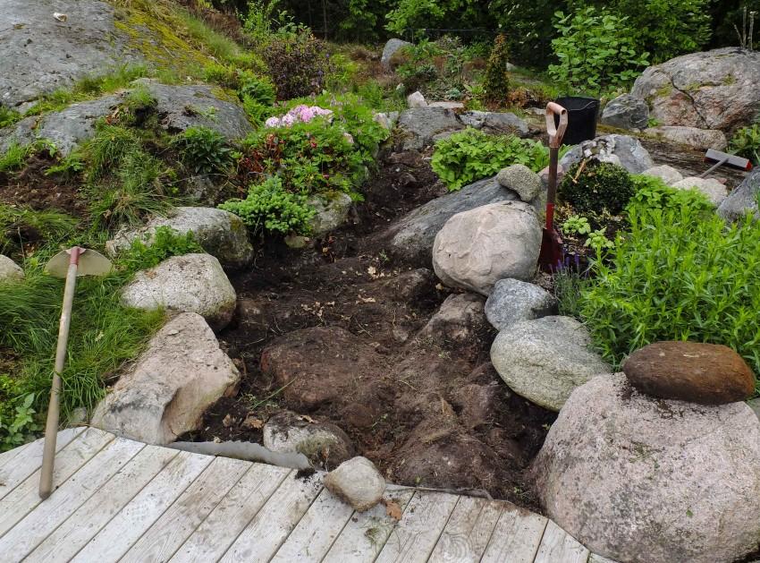 Fjern så mye som mulig av gresstorv og matjord, og planer så godt du kan. Beregn at du skal ha plass til 10 cm grus.